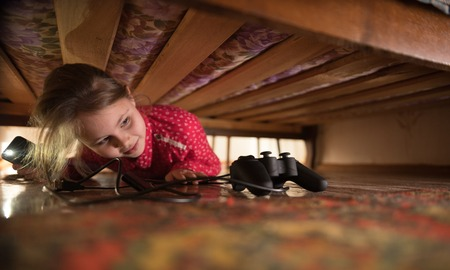 Joystick under the bed. Girl looking for it