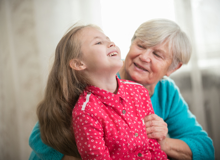 A girl spending time with her grandmother, laughing Stock Photo