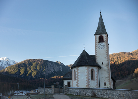 Dolomites nature. A church by the road. Clear blue sky and mountains. Mid shot