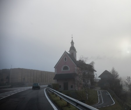 Dolomites nature. A church by the road. Foggy weather. Mid shot