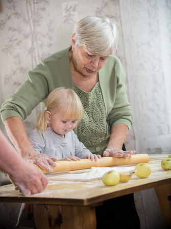 A grandmother making little pies with a little girl. Rolling the dough on a desk
