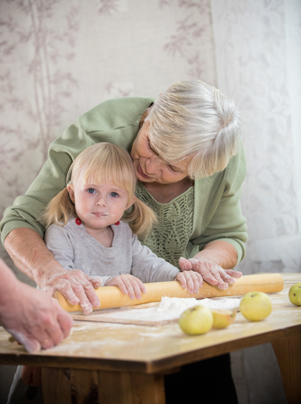 A grandmother making little pies with her granddaughter. Rolling the dough