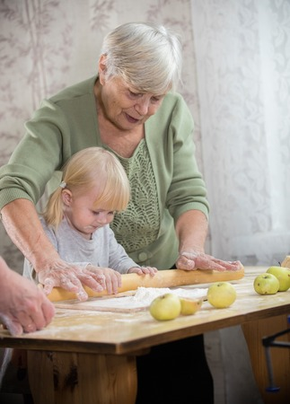 A grandmother making little pies with a little girl. Rolling the dough