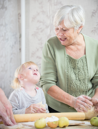 A grandmother making little pies with a little girl. Stock Photo