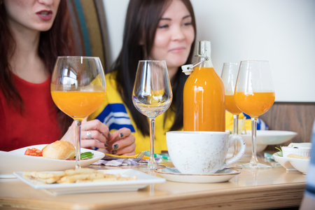 Group of young friends sitting in cafe. A bottle with juice Stock Photo