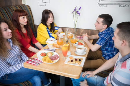 Group of young friends sitting in cafe by the table Stock Photo