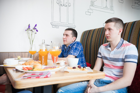 Group of young men friends sitting in cafe Stock Photo
