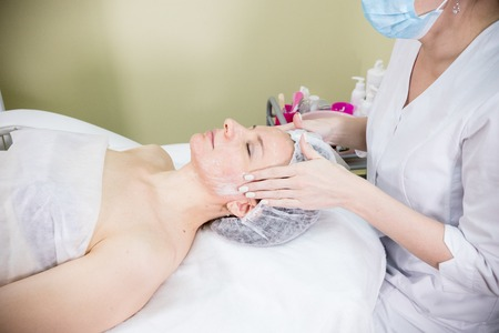 Cosmetologist prepares the clients face for cosmetic procedure of mesotherapy with cream Stock Photo