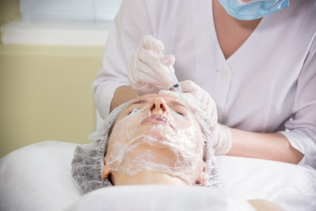 Cosmetologist working with clients face. Cosmetic procedure of mesotherapy. Doing injections in a forehead
