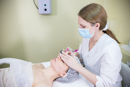 Cosmetologist prepares the clients face for cosmetic procedure of mesotherapy with soft stroking