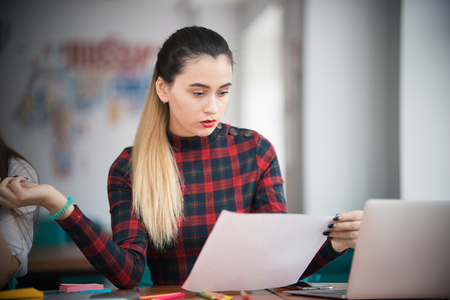 Young businesswoman working at office and looking at papers Stock Photo