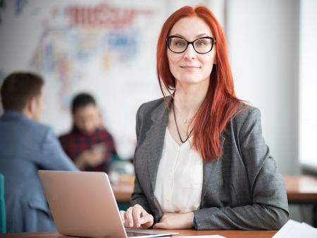 A ginger woman in glasses sitting at office and working by the laptop. Stock Photo