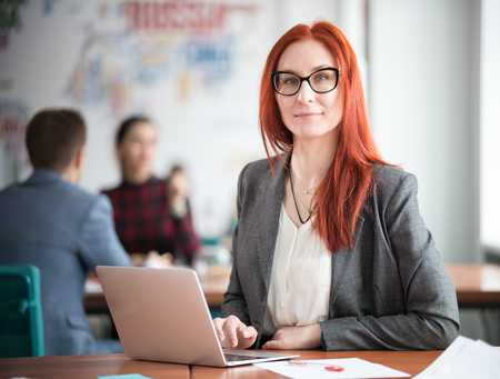 A ginger businesswoman in glasses sitting at office and working by the laptop. Looking in the camera