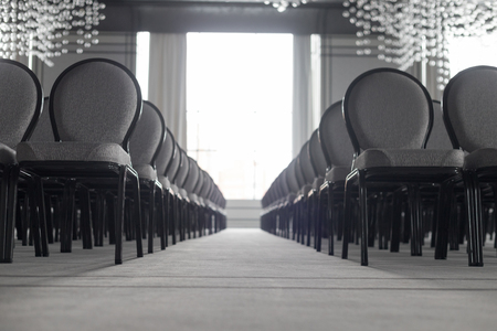 Empty conference hall. Straight rows of chairs. A white light coming from the window. Monochrome Stock Photo