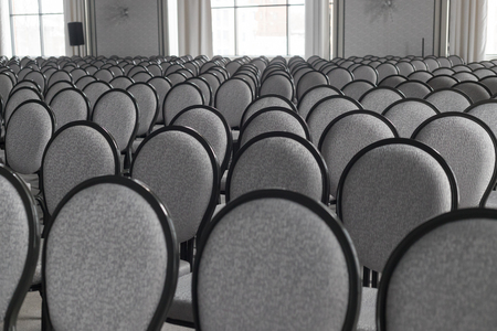 Empty conference hall. Empty rows of grey chairs. Monochrome