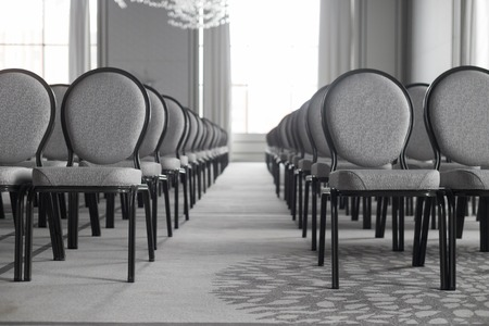 Empty conference hall. Straight rows of chairs. A symmetric corridor. Monochrome Stock Photo