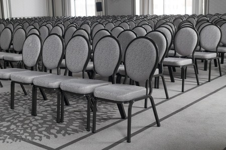 Empty conference hall. Empty rows of chairs. Monochrome