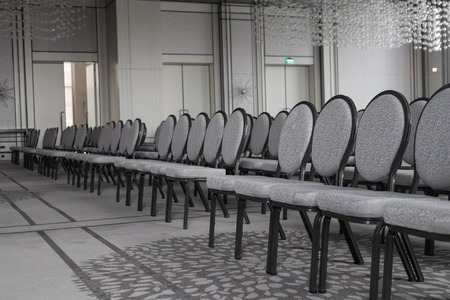 Empty conference hall. Straight rows of chairs. Monochrome