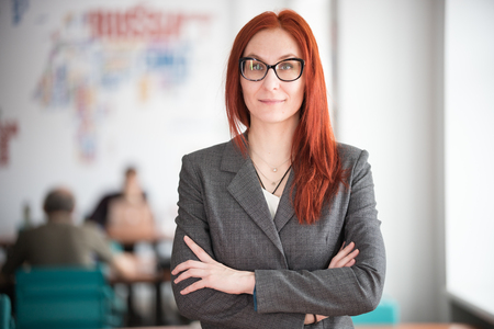 Education concept. Smiling ginger teacher woman in glasses standing in the office
