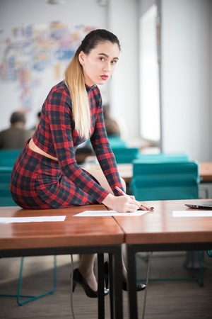 Young woman with red lipstick working sitting on a table in the office