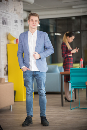 Young businessman in blue jacket standing at office
