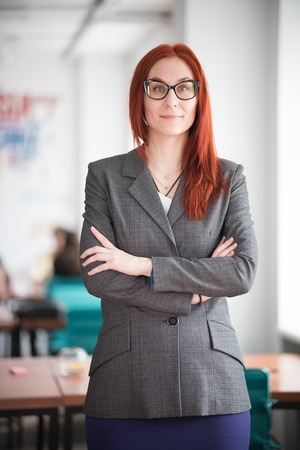 Education concept. Smiling ginger teacher woman standing in the office Stock Photo