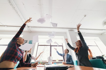 Excited business people throwing papers, documents fly in air