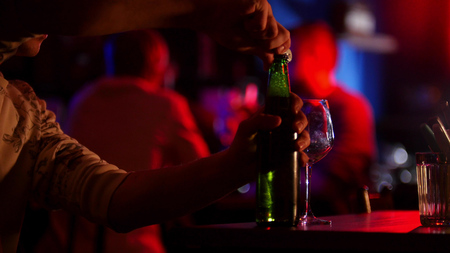 Bar with neon lighting. A man opens up a beer bottle