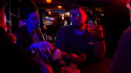 Bar con luces de neón. Grupo de amigos sentados en la mesa y bebiendo alcohol mientras habla Foto de archivo