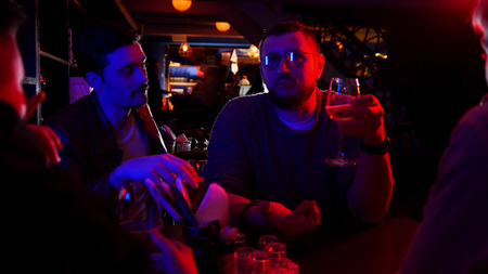 Bar with neon lighting. Group of friends sitting by the table and drinking alcohol while talking Stockfoto