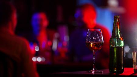 Bar con luces de neón. Una botella y un vaso de cerveza de pie sobre una mesa.