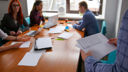 Business concept. A working team having a conference. A man brings the documents