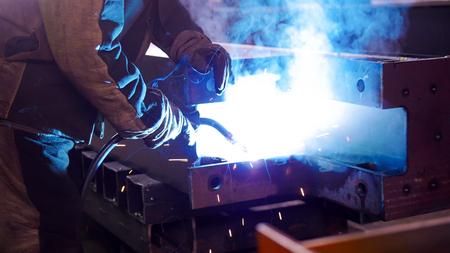 A man at the construction plant using a welding machine. Bright blue lighting Фото со стока