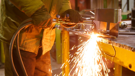 Construction plant. A man at his workplace using a welding machine. Heating up the side of the detail. Fire sparkles