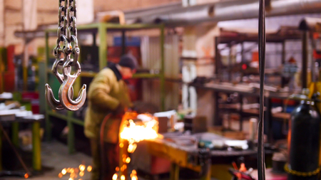 Construction plant. A big industrial lifting chain with a hook on the end. A man welding on the background Imagens