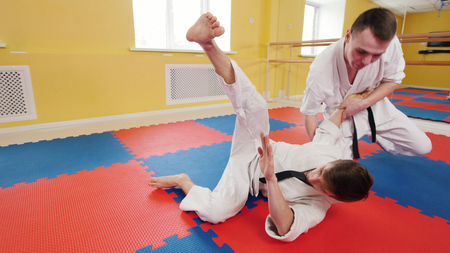 Two athletic men training their aikido skills in the studio. A man grabs his opponent and throws him on the floor Reklamní fotografie - 120886170