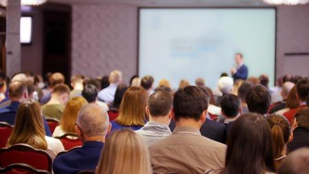 Een zakelijke conferentie in de hal. Mensen zitten op de stoelen en kijken naar de presentatie