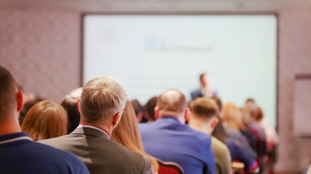 A business presentation in the hall. People sitting on the chairs and looking at the screen Standard-Bild - 120886842