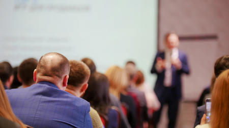 A business presentation. People sitting on the chairs and looking at the screen