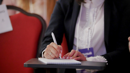 A business conference in the hall. A woman sitting by the table and making marks in the notebook