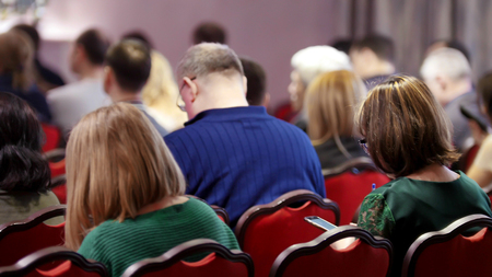 A business conference in the hall. People sitting on the chairs. Imagens