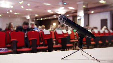 A business conference in the hall. People sitting on the chairs. A microphone on a foreground