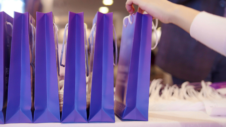 A business conference and presentation. Purple present package on a foreground. A person taking one of the packages