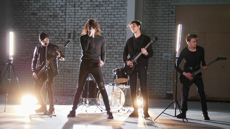 A rock group having a repetition in a garage. Members of a group wearing black clothes