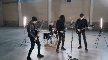 A young rock group having a repetition in a hangar. Members of a group wearing black clothes