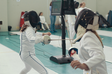 Two young girls fencers having fencing duel on tournament. Mid shot
