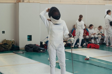 A girl fencer having fencing duel on tournament. A girl standing holding a saber