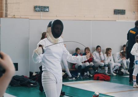 A girl fencer having fencing duel on tournament. A girl bending a saber