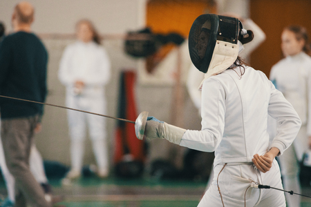 Young people fencers standing in the hall on a fencing tournament