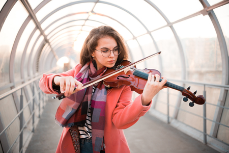 Young woman in glasses playing a fiddle on the overhead passage